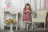 Little girl stands near a table — Stock Photo