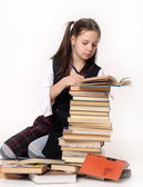 Girl schoolgirl with a large Number of books — Stock Photo