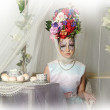 Beautiful girl with flowers on her head during a tea party — Stock Photo