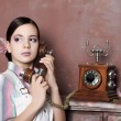 Girl holds up a vintage phone — Stock Photo