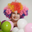 Girl with balloons in a colored wig — Stock Photo