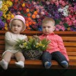 Children on a bench with flowers in the background — ストック写真
