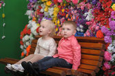 Children on a bench with flowers in the background — Stock Photo