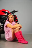 Thoughtful girl in pink on a background of motorcycle — Stock Photo