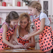 Mother with her daughters in the kitchen preparing pastries — Stock Photo