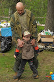 Paintballer with his son in a recreation area — Stock Photo