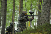 Paintballer while playing in the woods — Stock Photo