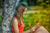 The girl on a grass with book — Stock Photo