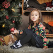 Little girl with gifts near a Christmas tree  — Stockfoto