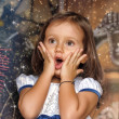 Surprised girl near the Christmas tree — Stock Photo