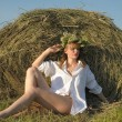 Young woman on the field with big hay bale rolls — Stock Photo #37227015