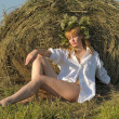 Young woman on the field with big hay bale rolls — Stock Photo #37227167