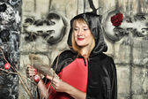 Woman in a red dress and a black cloak with a hood on Halloween — Foto de Stock