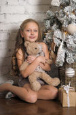 Girl near Christmas tree with toy — Stock Photo