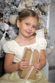 Girl near Christmas tree with gift box — Stock Photo