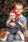Brother and sister near Christmas fir-tree — Stock Photo