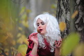 Beautiful young woman in the image of the witch in the woods on Halloween. — Stock Photo