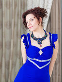 Portrait of elegant woman in stylish blue dress and  elaborate necklace, looking relaxed. — Stock Photo
