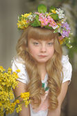 Beautiful young blond girl in a wreath of flowers — Stock Photo