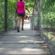 Woman walking over a suspension bridge - Foto de Stock