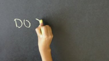A person writing with chalk on a blackboard Do you speak english?