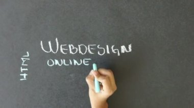 Person writing Web Design related words with chalk on a blackboard.