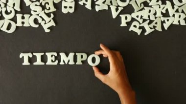 A person spelling time for change (In Spanish) with plastic letters