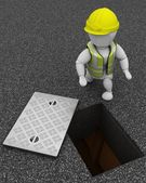Builder inspecting drains through manhole cover — Stok fotoğraf