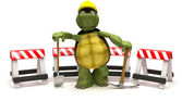 Tortoise with a spade and pick axe with hazard barriers — Stock Photo