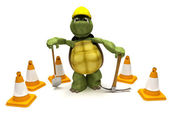 Tortoise with a spade and pick axe with hazard cones — Stock Photo