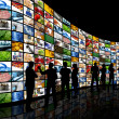 People looking at wall of screens — Stockfoto