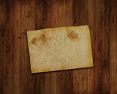 Old paper on grunge wood background — Stock Photo