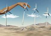 Hand placing wind turbines in a desert — Stock Photo