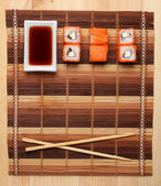 Two sticks and rolls on the sushi mat background for the menu — Stock Photo