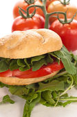 Sandwich with tomatoes and arugula — Stock Photo
