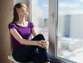 The beautiful woman sits near a window — Stock Photo