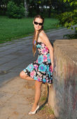 The beautiful young woman costs on avenue in summer park — Stock Photo