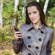 The beautiful woman with a mobile phone on walk in wood — Stock Photo #30662271