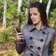 The beautiful woman with a mobile phone on walk in wood — Stock Photo