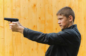 The teenager with a pistol — Stockfoto