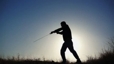 Silhouette of Guy Practicing With Sword — Stock Video