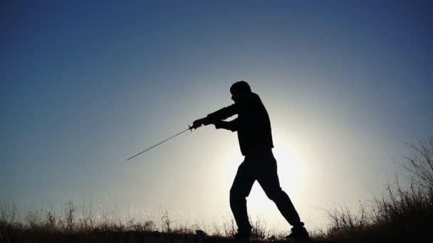 Silueta de tipo practicando con la espada — Vídeo de stock