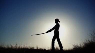 Silhouette of Girl Practicing With Sword — Stock Video