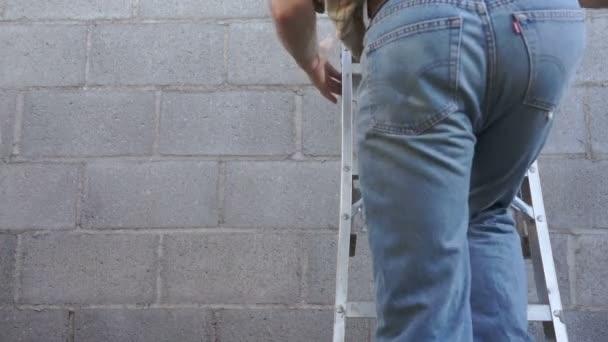 Hombre subiendo una escalera de mano — Vídeo de stock