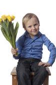 Jongen met tulpen is op zoek naar de camera — Stockfoto