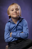 Boy in a blue shirt and black trousers on purple background — Stock Photo