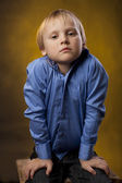 Boy in a blue shirt and black trousers on yellow background — Stock Photo