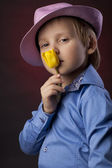 Boy in pink hat with yellow tulips — Stock Photo