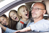 Happy father with children in the car — Stock Photo