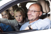 Huppy father with children in a car — Stock Photo